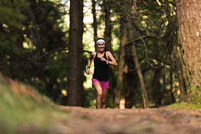 Young sportswoman running in forest - p300m2282634 by Mikel Taboada