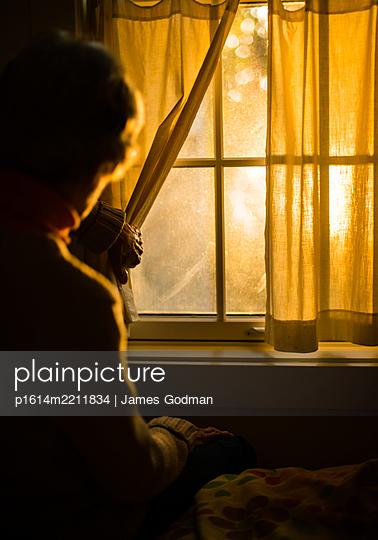 Ältere Frau schaut aus dem Fenster - p1614m2211834 von James Godman
