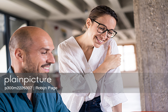 Smiling businesswoman standing by man at office - p300m2226307 by Robijn Page
