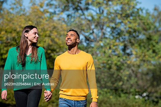 Smiling young couple walking together in public park - p623m2294844 by Eric Audras