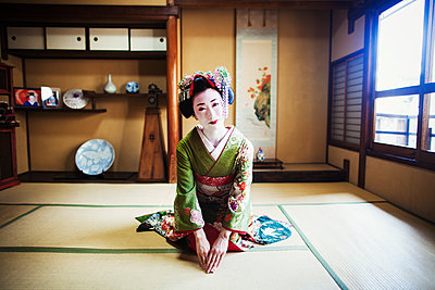 A woman dressed in the traditional geisha style, wearing a kimono and obi, with an elaborate hairstyle and floral hair clips, with white face makeup with bright red lips and dark eyes, kneeling in a traditional pose.  - p1100m1185744 by Mint Images
