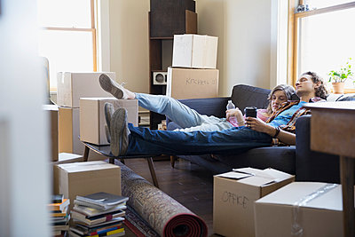 Couple relaxing on sofa surrounded by moving boxes - p1192m1031713f by Hero Images