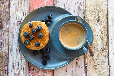 Dish with pancakes, blueberries with maple sirup and a cup of black coffee - p300m1228127 by Sandra Roesch