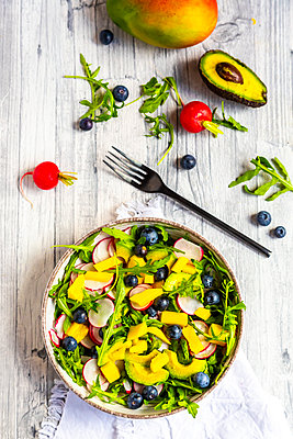 Bowl of rocket salad with mango, avocado, red radishes and blueberries - p300m2103775 von Sandra Roesch