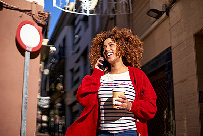 Smiling young woman with disposable coffee cup talking on mobile phone while standing against building - p300m2256714 by Veam