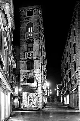 Narrow street and tall building at night in Venice - p3314008 by Thomas Ortolan