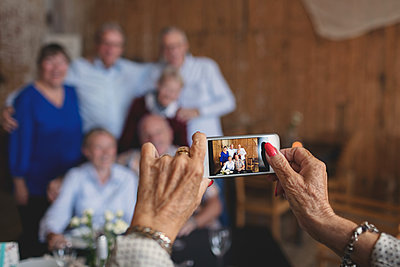 Cropped image of senior woman photographing friends with smart phone at restaurant - p426m1506297 by Maskot