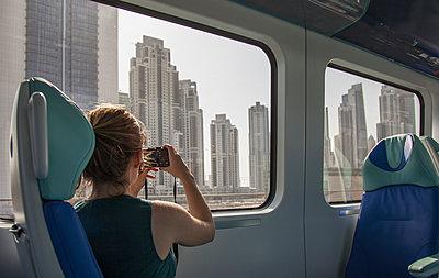 Caucasian woman photographing Dubai cityscape on train, Dubai Emirate, United Arab Emirates - p555m1410833 by ac productions