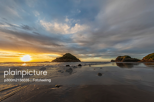 New Zealand, Tongaporutu, Cloudy sky over sandy coastal beach at sunset with Motuotamatea island in background - p300m2156035 by Fotofeeling