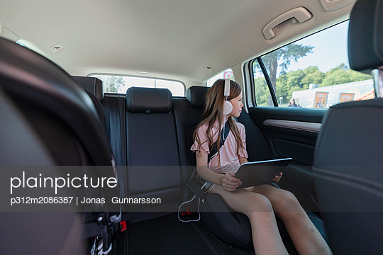 Girl with digital tablet in car - p312m2086387 by Jonas  Gunnarsson