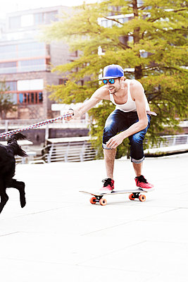 Skateboarder with dog - p1076m907870 by TOBSN