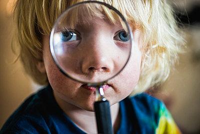Little boy looking through a magnifying glass - p1418m1591325 by Jan Håkan Dahlström