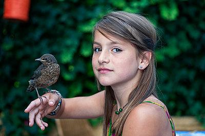 Mädchen mit einer Amsel auf der Hand - p1437m1502332 von Achim Bunz
