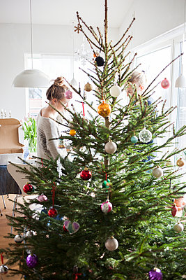 Girl decorating Christmas tree - p312m1470619 by Christina Strehlow