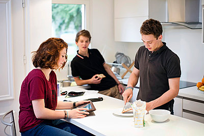 Young girl using digital tablet with male friends standing at kitchen counter - p426m766544f by Maskot