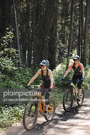 Women mountain biking on trail in sunny woods - p1192m2129208 by Hero Images