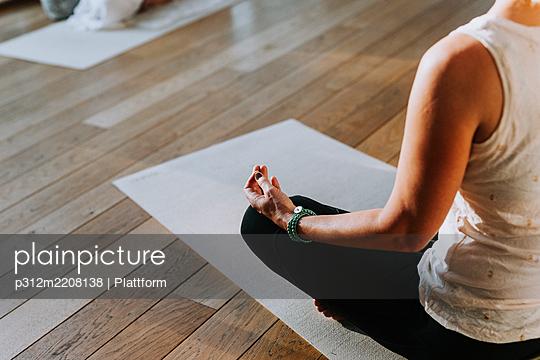 Woman meditating in yoga studio - p312m2208138 by Plattform