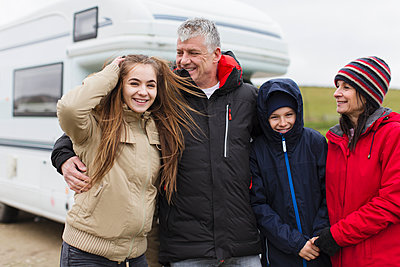 Portrait happy family in warm clothing outside motor home - p1023m2024293 by Sam Edwards