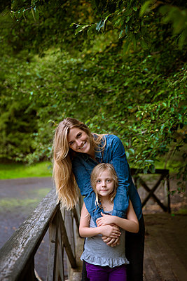 Portrait of smiling mother and daughter standing by railing against plants in yard - p1166m1096747f by Cavan Images