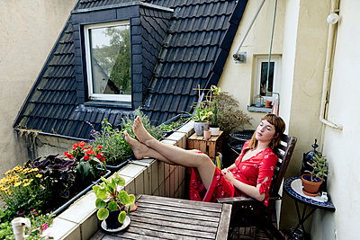 Portrait of pensive young woman relaxing with feet up on balcony - p300m2131850 by FL photography