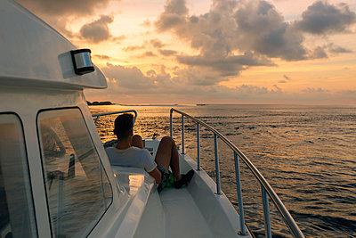 Man on sailboat at sunset, Thulusdhoo, Male, Maldives - p343m2047267 by Konstantin Trubavin