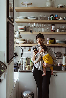 Mother text messaging on smart phone while carrying baby boy in kitchen - p426m2279901 by Maskot