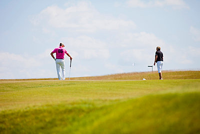 Two mature men playing golf at golf course - p426m747323f by Astrakan
