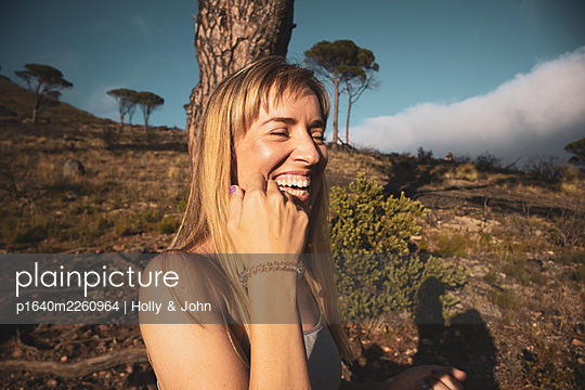 Laughing young woman in rocky landscape - p1640m2260964 by Holly & John