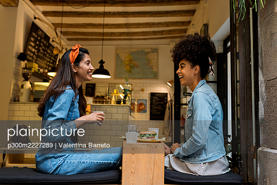 Smiling friends talking while sitting by window at cafe - p300m2227289 by Valentina Barreto