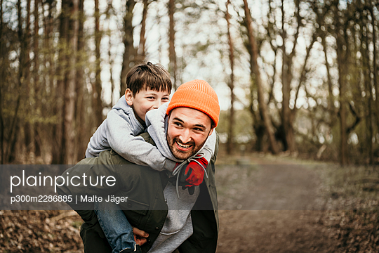 Father giving piggyback ride to son in forest - p300m2286885 by Malte Jäger