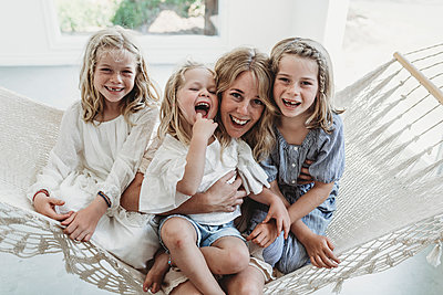 Mother and daughters cuddlin on hammock in natural light studio - p1166m2130898 by Cavan Images