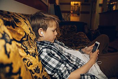 Caucasian tween boy with headphones using smart phone on old sofa - p1192m1516937 by Hero Images