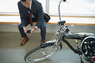 Businessman commuter texting with smart phone next to bicycle - p1192m1517070 by Hero Images