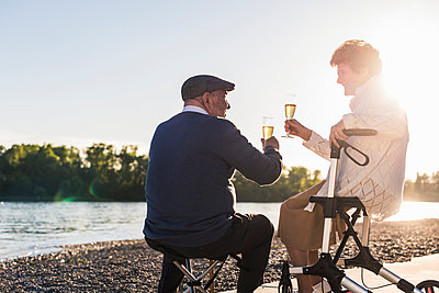 Senior couple toasting with sparkling wine at sunset - p300m1460352 by Uwe Umstätter