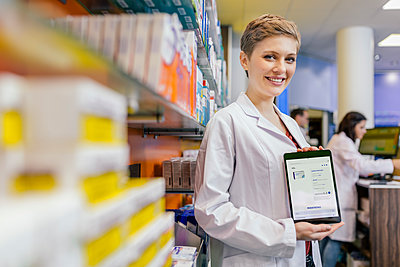 Portrait of smiling pharmacist in pharmacy holding tablet with digital order - p300m1549769 by Mareen Fischinger