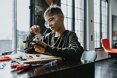 Boy assembling miniature helicopter at home - p300m2214196 by Mareen Fischinger