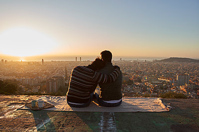 Gay boyfriends looking at cityscape against clear sky while sitting on observation point, Bunkers del Carmel, Barcelona, Spain - p300m2256684 by Veam