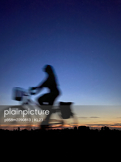 Woman riding a bike at sunset, blurred motion - p958m2290813 by KL23