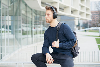 Young man with headphones on city street - p1166m2171504 by Cavan Images