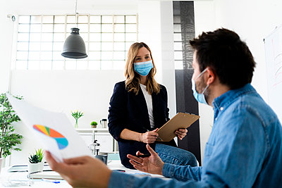 Business people wearing protective masks talking in office  - p300m2242595 by Giorgio Fochesato
