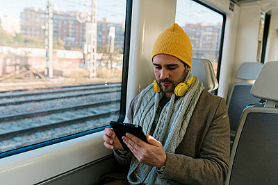 Mid adult man wearing warm clothing using digital tablet while sitting in train - p300m2251609 by Ezequiel Giménez