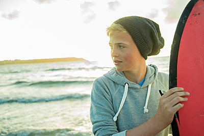 Portrait of teenage boy standing on the beach with his surfboard - p300m965472f by Uwe Umstätter