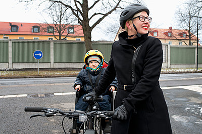 Sweden, Sodermanland, Stockholm, Woman holding bicycle with daughter (2-3) on back seat - p352m1186936 by Julia Sjöberg