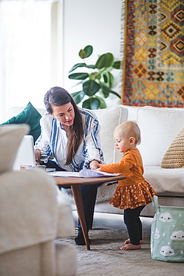 Working mother talking with loving daughter while managing her business from home office - p426m2117008 by Maskot