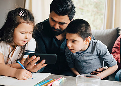 Father showing smart phone to children while woman using laptop on sofa in living room - p426m2118388 by Maskot