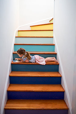 Caucasian girl using digital tablet on multicolor staircase - p555m1503999 by Adam Hester