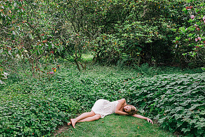 Young woman sleeps in clearing - p586m1055861 by Kniel Synnatzschke