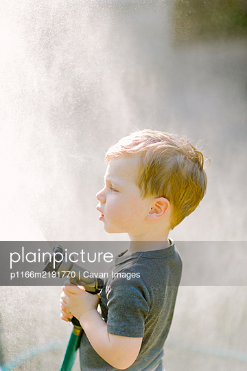 Little toddler boy playing with the garden hose - p1166m2191770 by Cavan Images