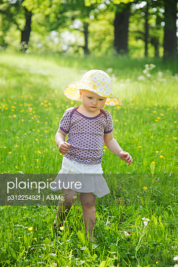 Girl wearing sun hat walking through meadow