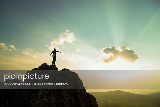 Caucasian hiker on rocky hilltop in remote landscape - p555m1411144 by Aleksander Rubtsov